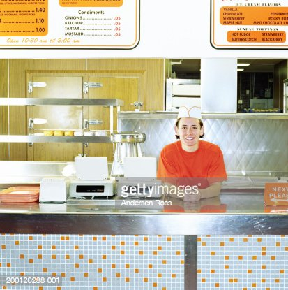 Teenage boy (17-19) working behind counter of fast-food restaurant
