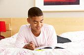 Teenage Boy Writing In Diary In Bedroom
