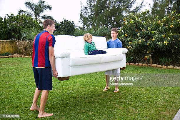 Teenage boys carrying toddler on white sofa
