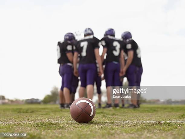 Teenage boys (16-18), football players in huddle on field