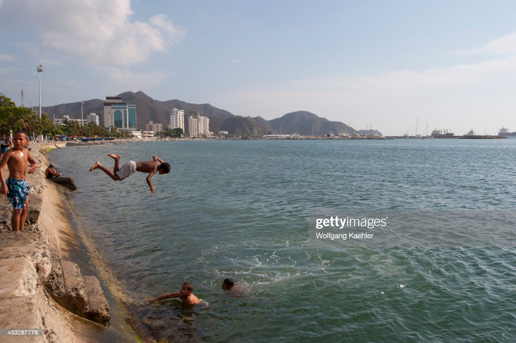Teenage boys jumping into water from beach promenade of Santa Marta Colombia
