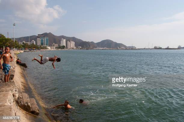 Teenage boys jumping into water from beach promenade of Santa Marta Colombia