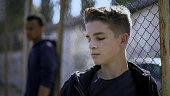 Teenage boys leaning on metal fence, juvenile detention center, orphanage