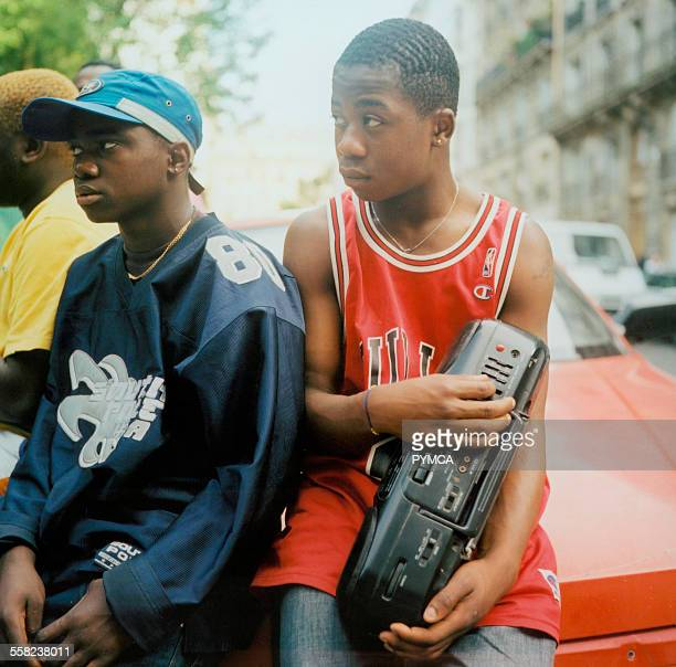Teenage boys listening to music friom a stereo wearing American style football and basketball tops in Paris