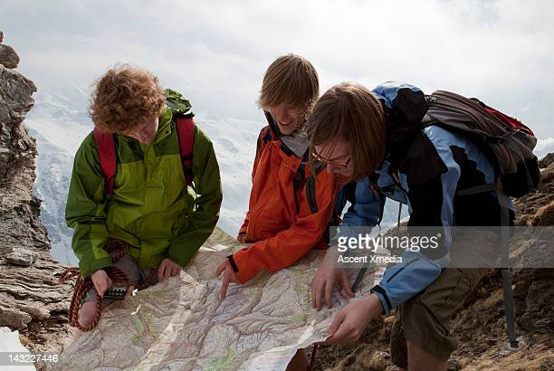 Teenage boys look over map, compass to plot route