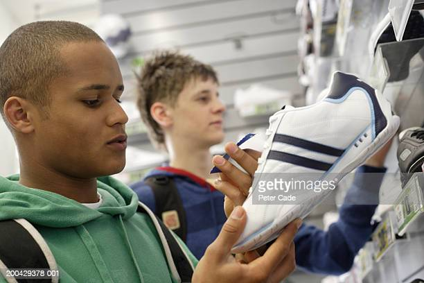 Teenage boys (16-18) looking at training shoes in shop