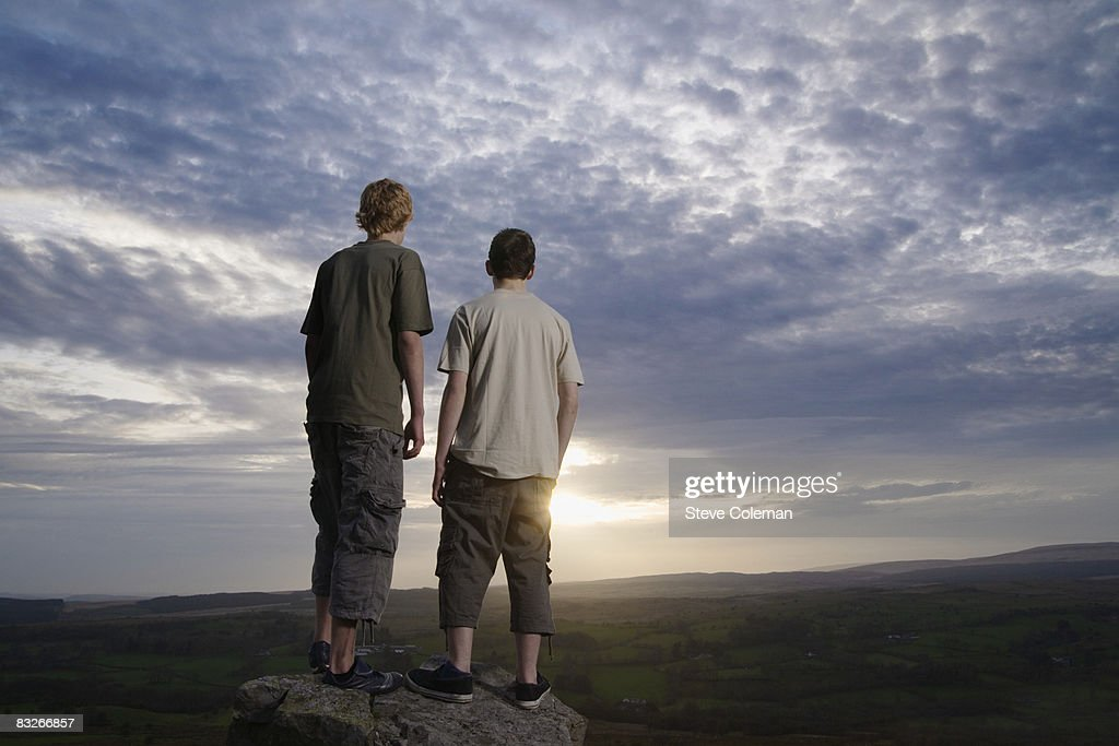 Teenage boys on rock viewing countryside : Stock Photo