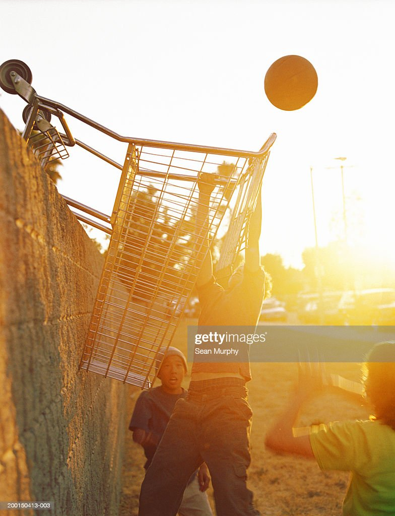 teenage boys playing basketball using grocery cart for hoop stock
