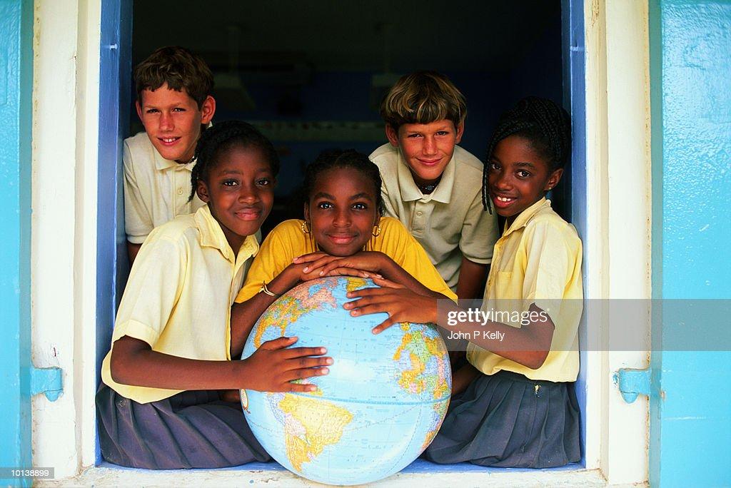 Teenage boys (12-14) posing around large globe : Stock Photo