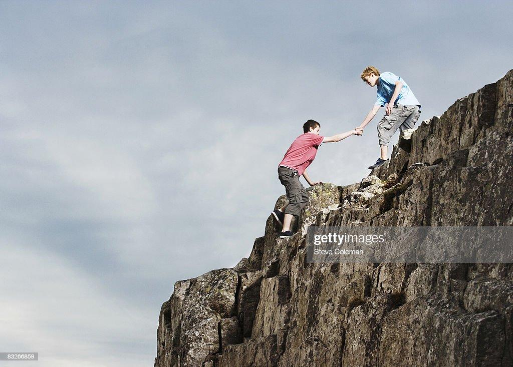 Teenage boys rock climbing : Stock Photo
