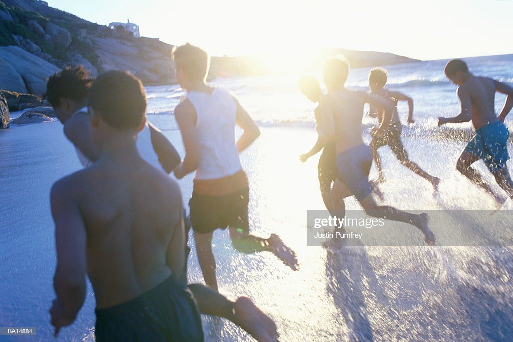 Teenage boys (14-16) running through surf on beach, rear view : Stock Photo