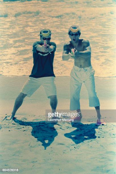 Teenage Boys Shooting Squirt Guns at Beach