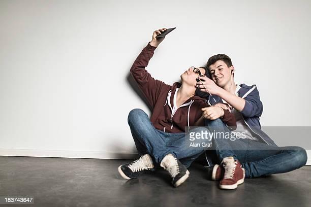 Teenage boys sitting cross legged leaning against wall using smartphones