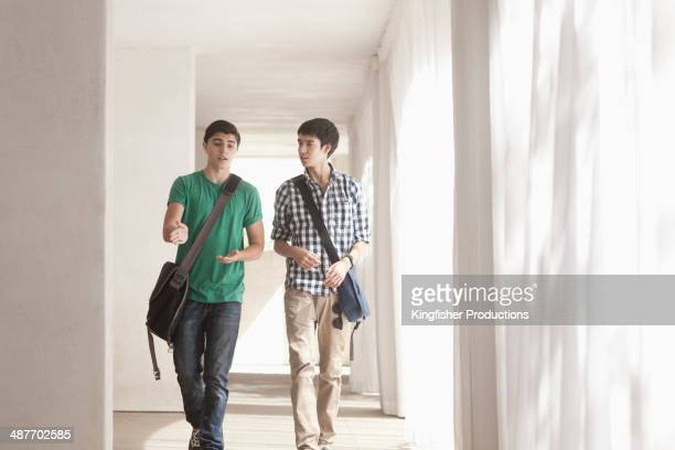 Teenage boys talking in corridor
