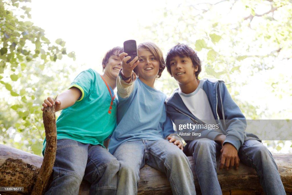 Teenage boys using smart-phone camera : Stock Photo