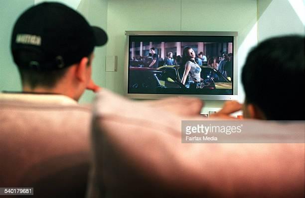 Teenage boys watch a movie on a digital television