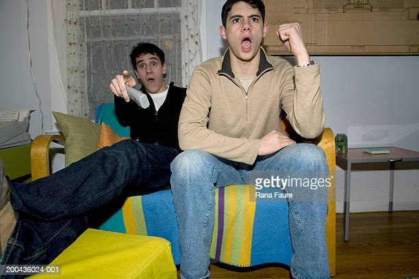 Teenage boys (17-19) watching television, one holding remote control