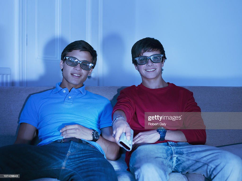 Teenage boys watching television with 3-D glasses : Stock Photo