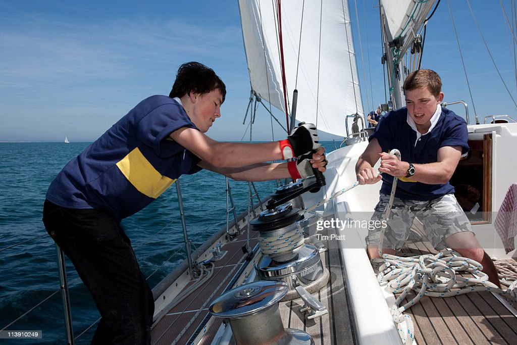 Teenage boys winching a rope on a sailing yacht. : Stock Photo