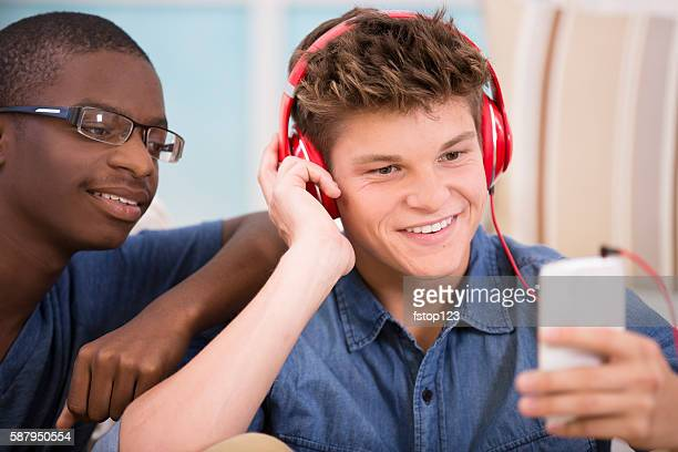 Teenage boys with headphones, smart phone at home.