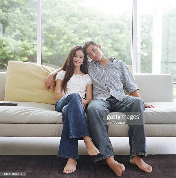 Teenage brother and sister (13-15) sitting on couch,  portrait