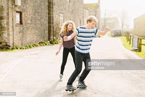 Teenage brother and sister skateboarding on rural road