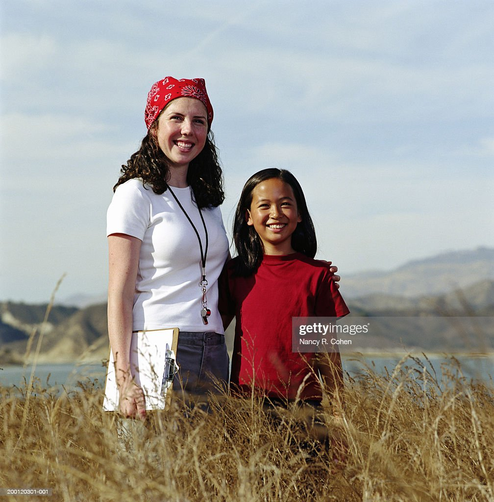 Teenage camp counselor with arm around girl (8-10), portrait : Stock Photo