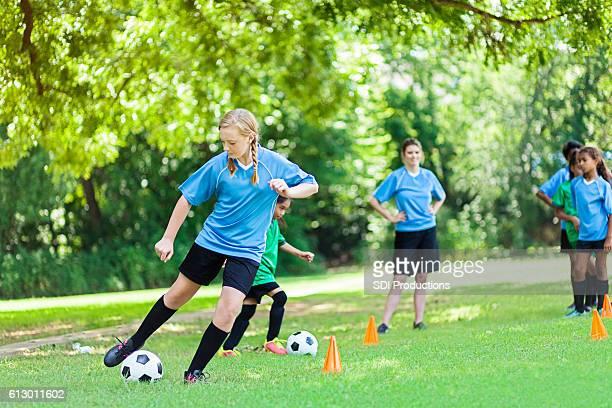 Teenage Caucasian soccer player kicks ball during practice
