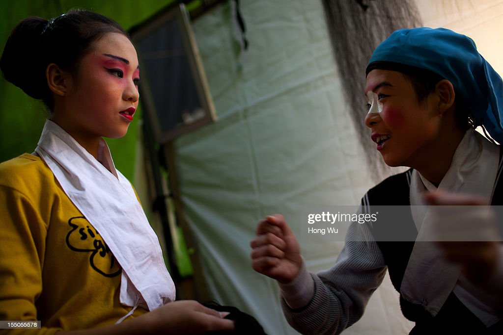 Teenage Chinese Yu Opera performers prepare backstage on October 30, 2012 in Zhengzhou, China. As many as 60 performers from the Sanmenxia theatrical troupe are invited to perform Chinese traditional Yu Opera for local villagers in rural Zhengzhou city to celebrate the village's temple fair and earn 10,000 RMB yuan (US$ 1,600) each performance. Yu Opera, also called Henan Bangzi or Ou Opera, is one of the most popular local operas in China. Its earliest written record can be traced back more than 200 years and at the end of the Qing Dynasty (A.D. 1644-1911), the opera became widespread across the Henan province. After the establishment of the People's Republic of China in 1949, it experienced rapid growth not only in the villages and cities of Henan Province but also throughout the country. In recent years its popularity has declined due to young people's attraction to more modern cultures.