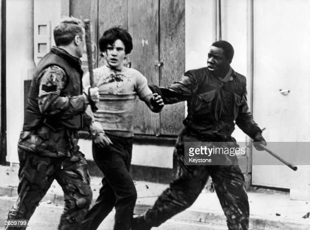 A teenage civilian is arrested by British troops during a civil rights demonstrations in Belfast