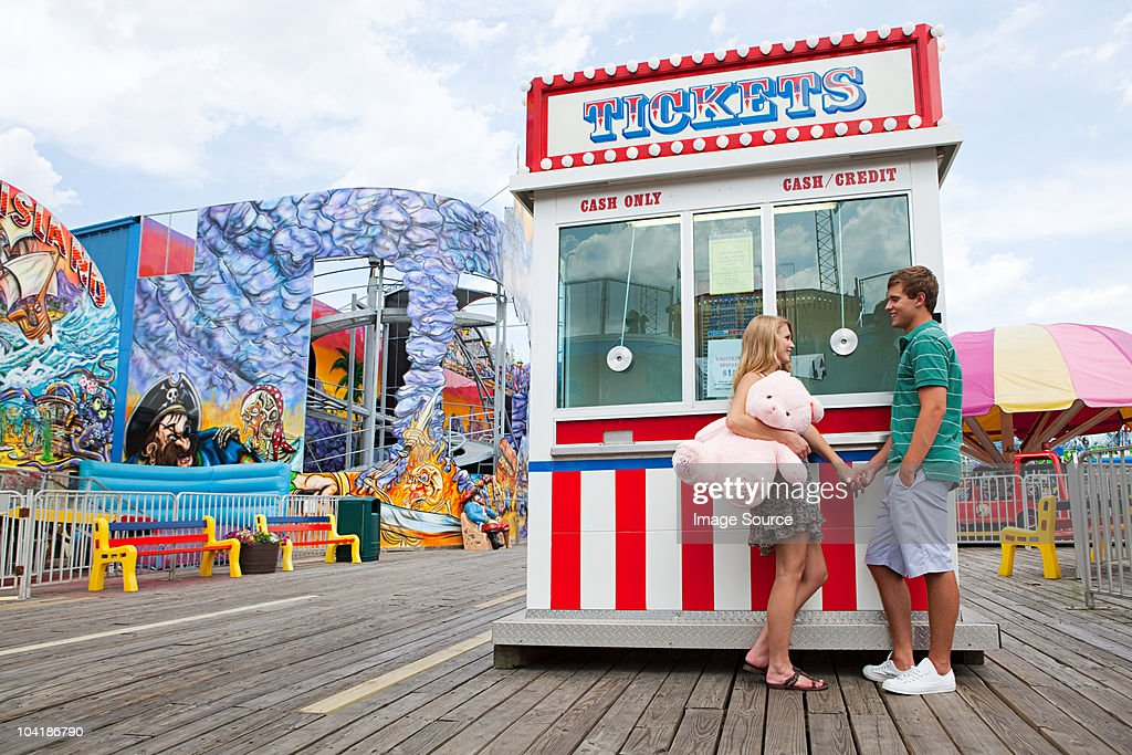 Teenage couple at fun fair ticket booth