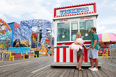 Teenage couple at fun fair ticket booth