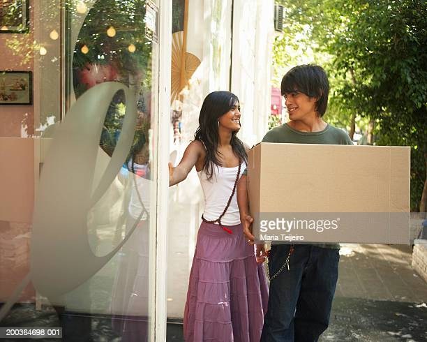 Teenage couple (16-18) by shop, boy carrying box