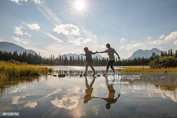 Teenage couple cross lake on stepping stones
