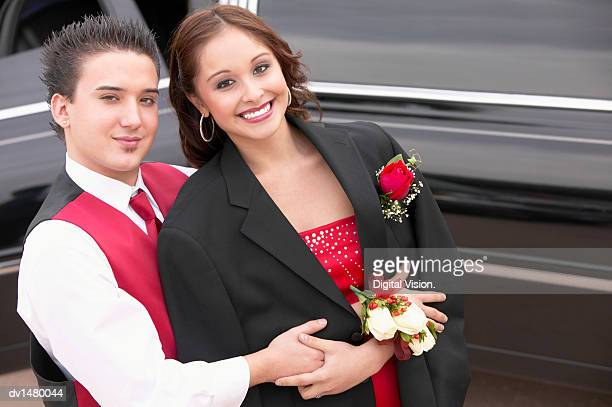 Teenage Couple Dressed for Their School Prom Standing by a Limousine
