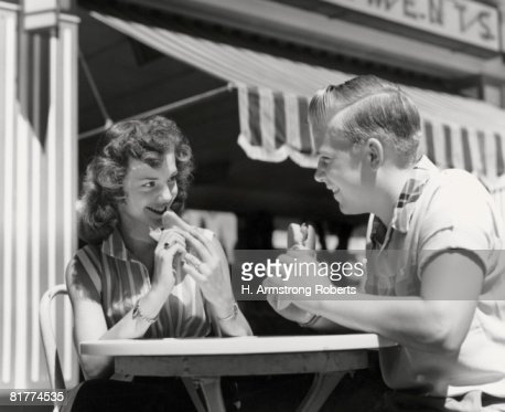 Teenage couple eating hotdogs outside at refreshment stand table. : Stock Photo