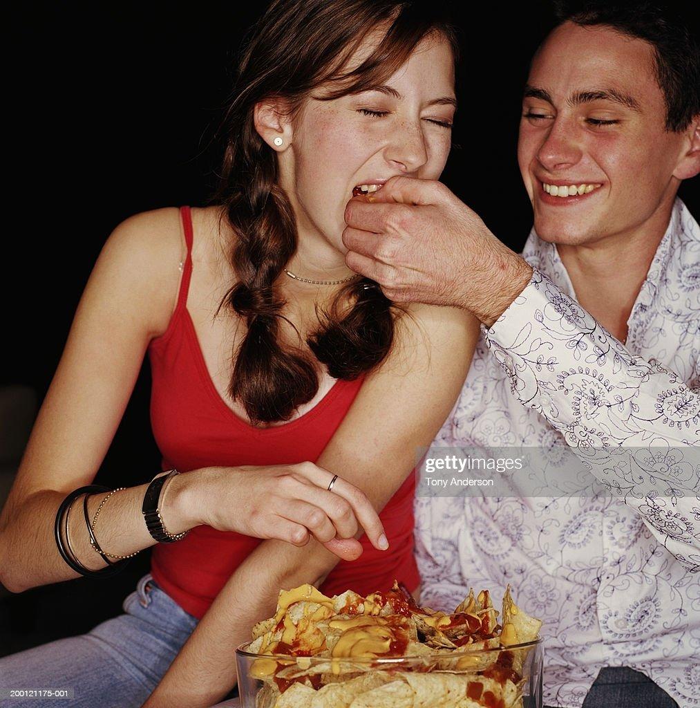 Teenage couple (15-18) eating nachos