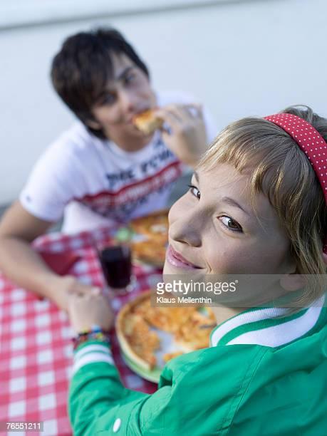 Teenage couple (16-17) eating pizza, girl smiling