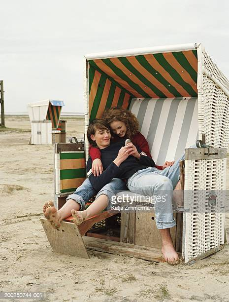 Teenage couple (15-19) embracing in hooded beach chair, smiling