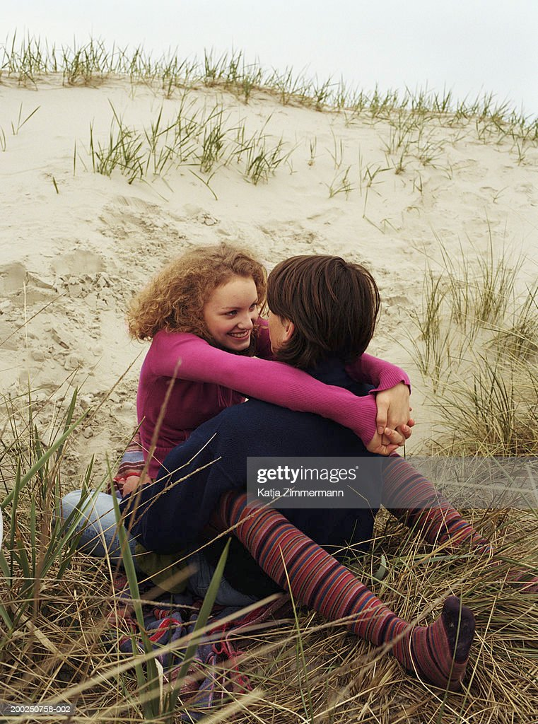 Teenage couple (15-19) embracing on sand dune, smiling, close-up