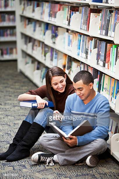 Teenage couple hanging out in library