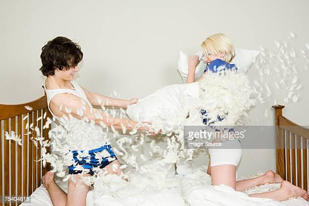 Coppia di adolescenti avendo una Lotta con cuscino