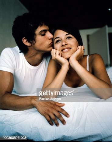 Teenage couple in bed boy kissing girl stock photo getty for Boys and girls in bed