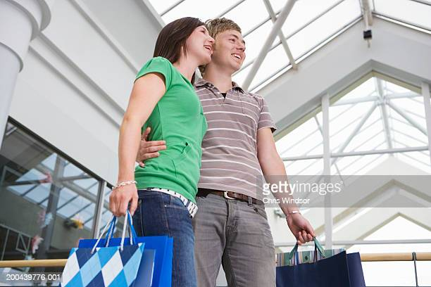 Teenage couple (15-17) in shopping centre with bags, low angle view