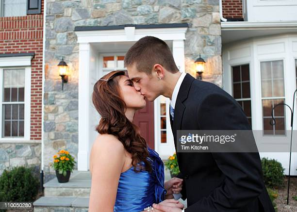 Teenage couple kiss in front of house before prom