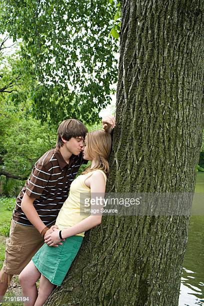 Teenage couple kissing near tree