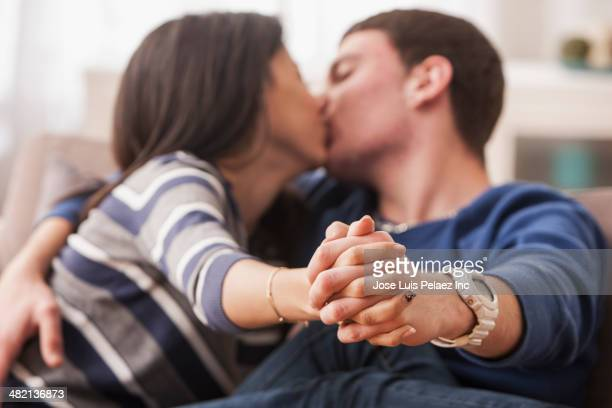 Teenage couple kissing on sofa
