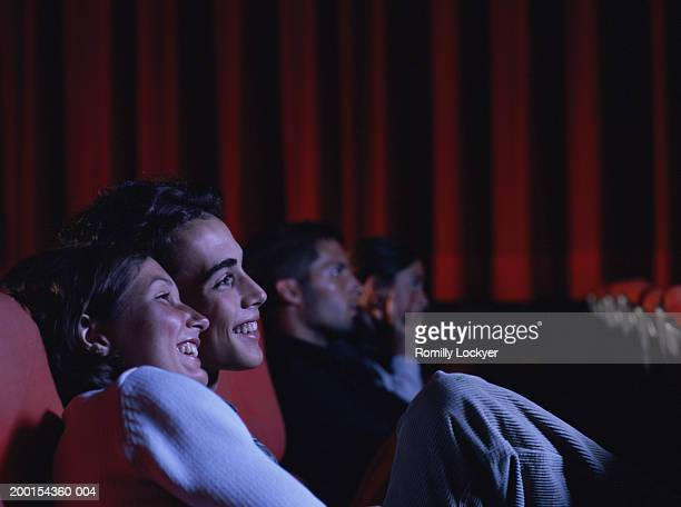 Teenage couple (16-18) laughing in auditorium, side view