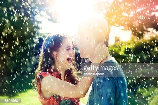 Teenage couple laughing in rain