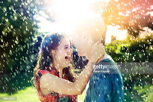 Teenage couple laughing in rain